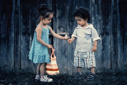 A picture of one child giving to another in an article on the Church of Christ Santa Clara website in an article about service and doing unto others