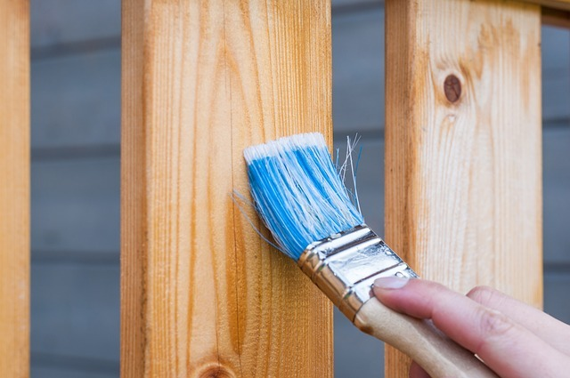 Photo of a hand staining a fence in an article on restoration on the Church of Christ Santa Clara Truthseekers SCCOC website.